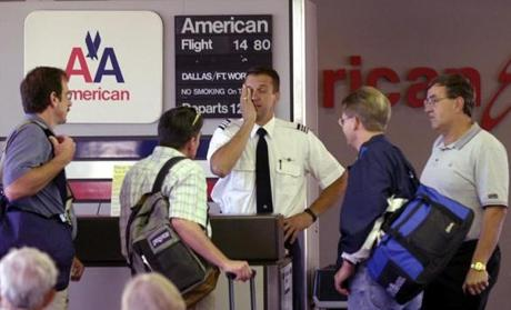 American AIrlines first officer Sean Pavlich, center, hand on face, answers travelers questions after their flight had been returned to Mid-Continent Airport in Wichita, Kan., Tuesday, Sept. 11, 2001. Air traffic around the country was halted after attacks on the World Trade Center in New York and on the Pentagon in Washington, both involving airplanes. (AP Photo/The Wichita Eagle, Mike Hutmacher) wtc9112001 airlinegallery